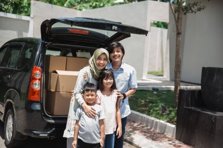 Photo for Family with two kids smiling to camera ready to move to the new house - Royalty Free Image