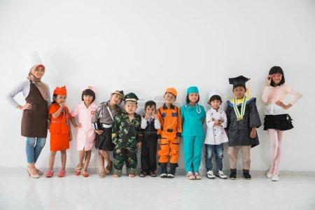 Photo pour Groupe d'enfants vêtus de costumes de différentes professions sur fond blanc ensemble - image libre de droit