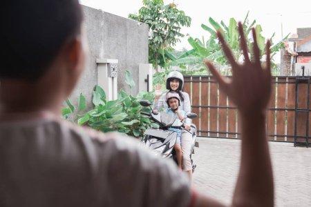 Photo pour Portrait de la mère et la fille CIRC. moto scooter ondulant au revoir à papa - image libre de droit