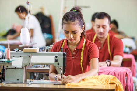 Portrait of professional Seamstress in textile fac...
