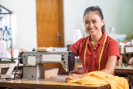 Portrait of Seamstress in textile factory smiling ...