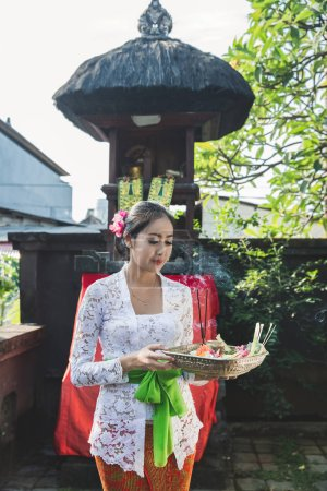 balinese woman praying and offerings canang sari at temple on sm