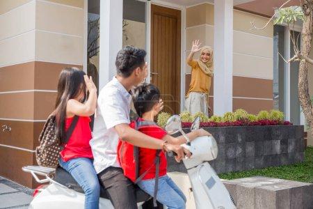 Photo pour Portrait de papa prenant ses enfants à l'école de moto, ondulant au revoir à maman - image libre de droit