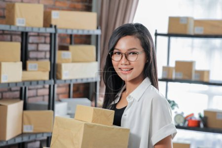 Woman courier holding package work at shipping package business