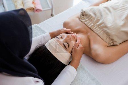 Young woman enjoying massage with mask cream
