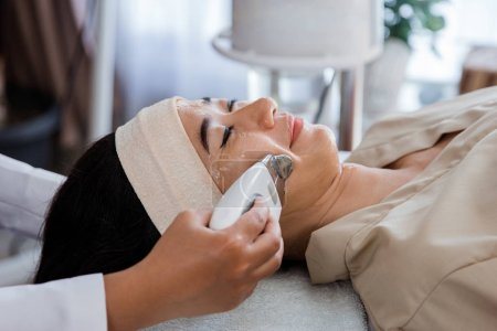 Picture of beautician doing rf procedure for women laying in a beauty salon