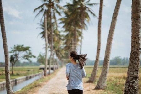 a woman ran in side coconut trees