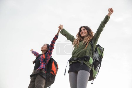 Photo for Two Freedom traveler woman standing with raised arms and enjoying a beautiful nature - Royalty Free Image