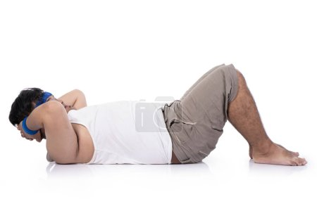 Photo for Young obese men have difficulty doing sit up before starting core training - Royalty Free Image
