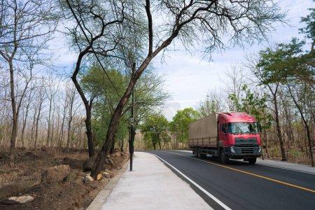 Photo pour Portrait de camion remorque dans la campagne route avec des arbres autour - image libre de droit