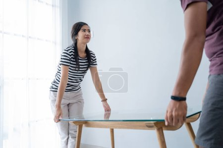 Photo for A new couple brings a table to move interior furniture in the living room - Royalty Free Image