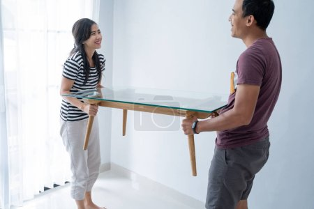 Photo for New couples together lift the table to fill the furniture in the living room - Royalty Free Image