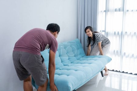 Photo for Husband and wife lifting a couch to help her husband arrange the living room - Royalty Free Image