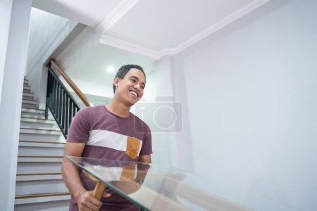Photo for Young asian man move a table upstair with friend or partner - Royalty Free Image