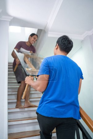 Photo for Two man helped each other lifting a table by climbing up the stair - Royalty Free Image