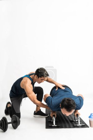 Trainer accompanies a man doing push up exercises ...
