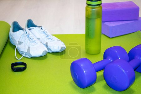 Photo for Fintes dumbbells, sneakers, a bottle of water, fitness bracelet and purple cubes on a green mat, sports concept, horizontal photo - Royalty Free Image