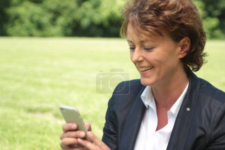 Businesswoman using mobile phone in park