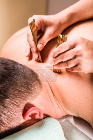 Close view of massage therapist doing deep tissue body massage therapy for male neck