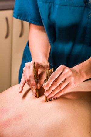 Close view of massage therapist doing deep tissue body massage therapy for male back