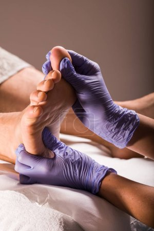 Massage therapist doing deep tissue body massage for male foot