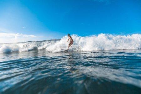 Photo pour Jeune homme athlétique chevauchant sur les vagues par une journée ensoleillée - image libre de droit