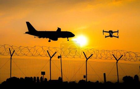 Foto de Drone no tripulado volando sobre la valla de seguridad en el aeropuerto mientras el avión comercial se prepara para el aterrizaje, lleva a la posible colisión - compuesto digital - Imagen libre de derechos