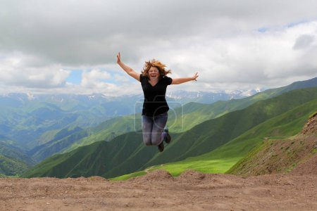 Photo pour Femme en tenue noire, un touriste sauta, étendit les bras sur le col de la Croix de l'Ours, montagnes de Géorgie - image libre de droit