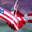 Handshake of two hands with Danish and USA flags o...