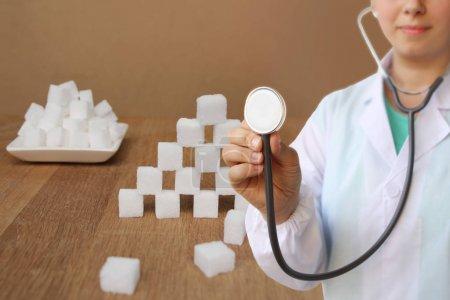 Photo pour Médecin diététiste en uniforme blanc avec un stéthoscope dans ses mains, suivi d'un cube blanc de sucre sur un linge de lit, concept de l'excès de sucre, diabétique, gros plan, espace de copie - image libre de droit