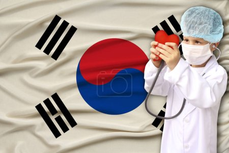 Photo pour Child, boy, in a white doctors coat, hat and mask attached a stethoscope to a red heart model, South Korea flag background, close-up, face focus, medical, cardiology concept - image libre de droit