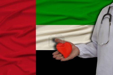 Photo pour Photo d'un médecin portant un stéthoscope en uniforme professionnel avec un cœur à la main sur le fond du drapeau national de l'État d'Uae, concept de soins de santé, traitement, assurance médicale - image libre de droit