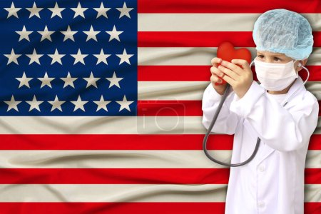 Photo pour Child, boy, in a white doctors coat, hat and mask attached a stethoscope to a red heart model, Denmark flag background, close-up, face focus, medical concept, cardiology, copy space - image libre de droit