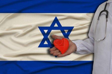 Photo pour Photo d'un médecin avec un stéthoscope avec un cœur dans la main sur le fond du drapeau national d'Israël, le concept de soins de santé, le traitement cardiologique, l'assurance médicale - image libre de droit