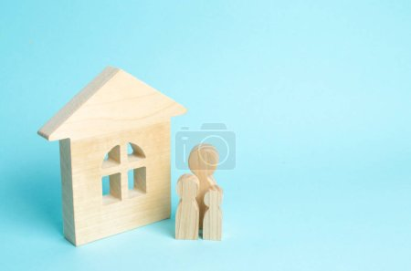 Family is standing near the house. Wooden figures of persons stand near a wooden house. The concept of a couple in love, cohabitants, parents, buyers and sellers at home. They live in the house