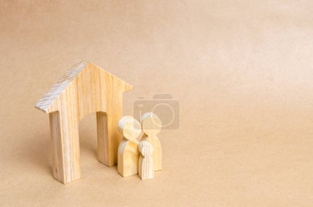 Family is standing near the house. Wooden figures of persons stand near a wooden house. The concept of a couple in love, cohabitants, parents, buyers and sellers at home. They live in house