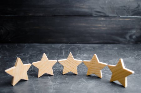 Five wooden stars. Get the fifth star. The concept of the rating of hotels and restaurants, the evaluation of critics and visitors. Quality level, good service. selective focus