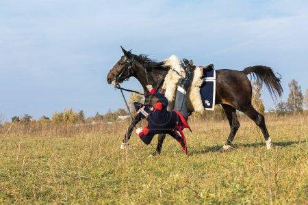 Photo pour 07.10.2018 Russie, Moscou. Homme caucasien en bleu national avec une combinaison militaire rouge des dernières années à cheval noir a sauté à travers un obstacle dans le domaine et tombe d'un cheval - image libre de droit