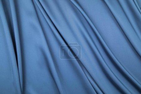 Foto de El corte sateen de tela azul se extiende por los pliegues suaves drapeados - Imagen libre de derechos