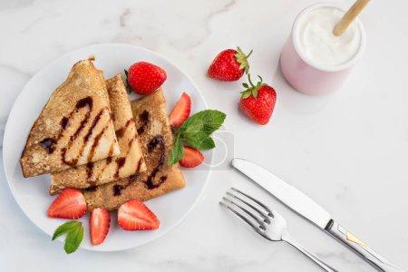 Photo pour Crêpes à la sauce au chocolat, décorées de fraises. Couverts et une tasse de crème sure - image libre de droit