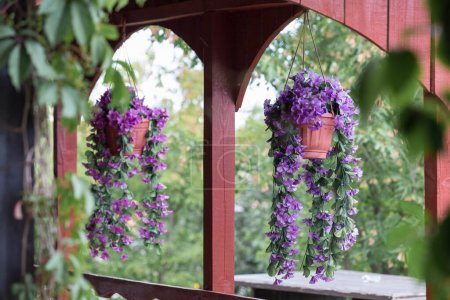 Pots of flowers are suspended in the opening of th...