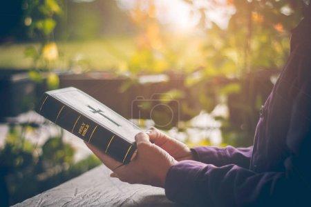 In Großaufnahme der Hände hält das gottgläubige Mädchen die heilige Bibel mit Deckel, um das Kreuz zu formen, das ein Symbol der Liebe und Barmherzigkeit Gottes gegenüber allen Menschen ist. in der Sonne am Abend.