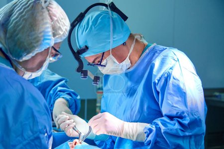 Photo for Surgeon and his assistant performing cosmetic surgery in hospital operating room. Surgeon in mask wearing loupes during medical procadure. Breast augmentation, enlargement, enhancement - Royalty Free Image