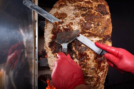 Photo pour Viande frite sur une brochette pour la cuisson des donneurs ou du shawarma. ook mains gros plan coupe la viande dans la mince sli e - image libre de droit