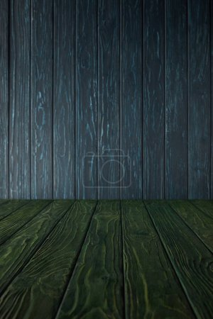 green wooden table and dark blue wooden wall