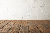 brown wooden surface and white wall with bricks