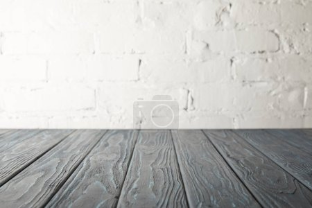Photo for Grey wooden tabletop and white wall with bricks - Royalty Free Image