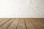 brown wooden tabletop and white wall with bricks