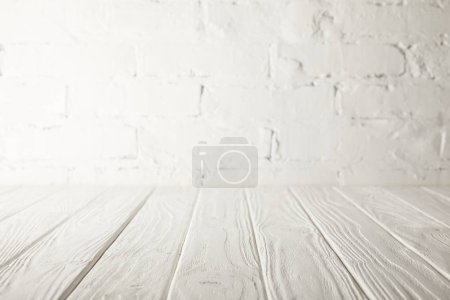 Photo for White wooden tabletop and white wall with bricks - Royalty Free Image