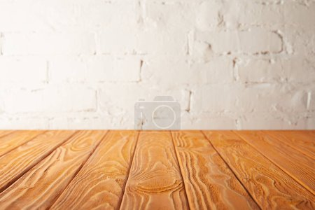 Photo for Orange wooden tabletop and white wall with bricks - Royalty Free Image